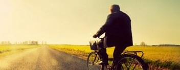a man cycles into the sunset